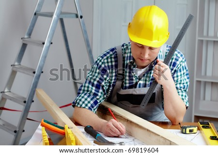 A young repairmen sitting at table and working with a plan - stock photo