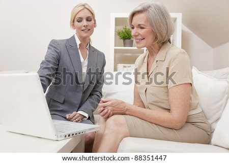 A young saleswoman showing a senior woman medical insurance or pension information on a laptop computer - stock photo