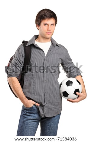 A young school boy carrying a school bag and holding a football isolated on white background - stock photo