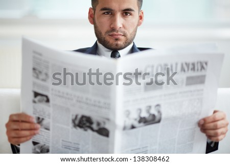 A young serious businessman looking at camera while reading newspaper
