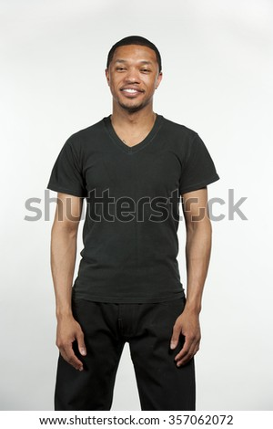 A young serious hip African American male wearing a black t-shirt in a studio setting on a white background. - stock photo