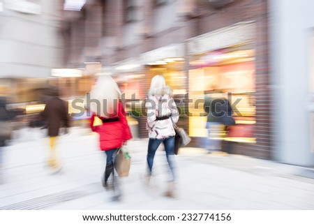 A young shoppers walking against shop window  - stock photo