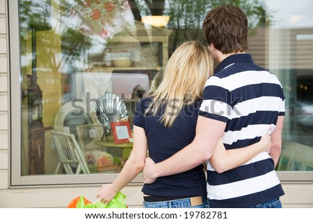 A young shopping caucasian couple looking into a store - stock photo