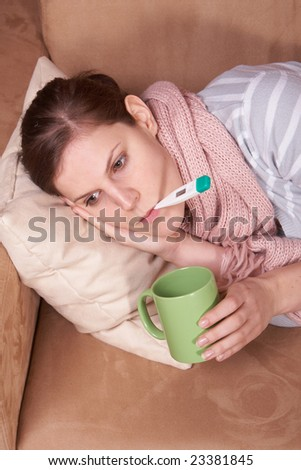 A young sick woman with a thermometer in her mouth and with a cup of tea in her hand. - stock photo