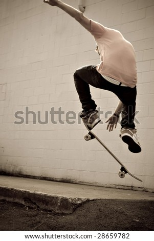 A young skateboarder doing a stunt in an urban area. - stock photo