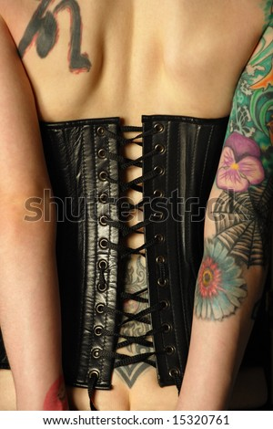 A young slim women with arm and back tattoos dressed in a black leather corset.  Focus is on the middle of corset. - stock photo