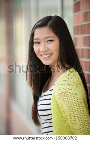 A young smiling beautiful Asian girl leaning against a wall