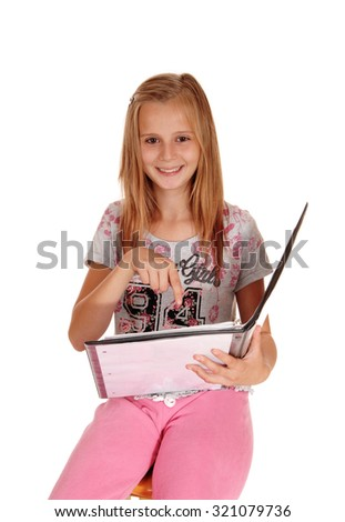 A young smiling blond girl sitting in a pink pants, holding her folderand pointing at her work, isolated for white background. - stock photo