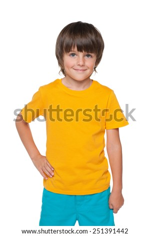 A young smiling boy in a yellow shirt stands on the white background