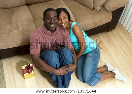 A young smiling couple sitting on the floor by a gift box in front of a sofa.