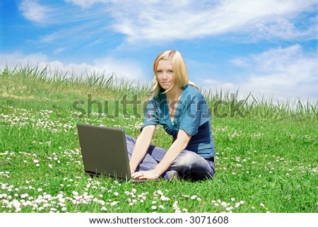 a young smiling woman is sitting on a meadow with her notebook