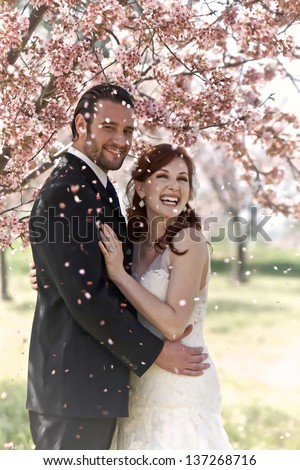 A young 30 something bridal couple hold each other in a loving embrace while being showered by petals from the blooming cherry blossom tree they are standing under. - stock photo