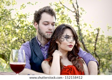 A young 20-something couple relax in a loving embrace while on a picnic in the park  - stock photo