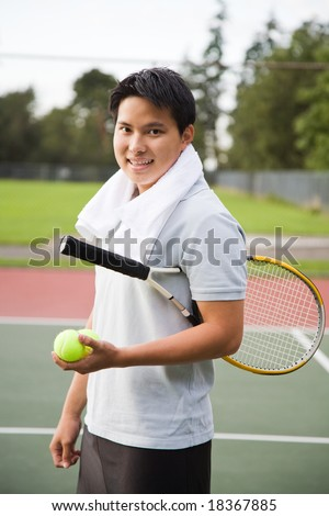 A young sporty Asian male playing tennis - stock photo