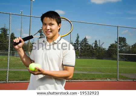 A young sporty asian man playing tennis