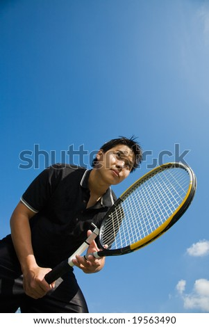 A young sporty asian tennis player receiving serve - stock photo