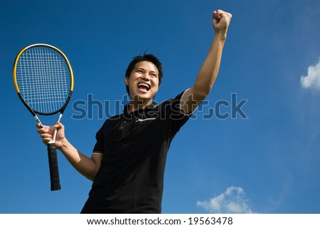 A young sporty asian tennis player screaming in joy of victory