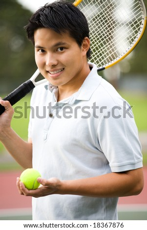 A young sporty casual Asian male playing tennis - stock photo