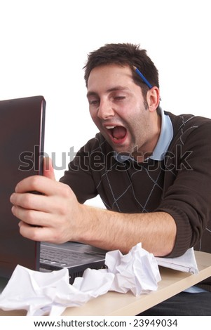 A young stressed out man is screaming at his laptop in anger. Isolated over white. - stock photo