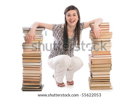 A young student sitting beside a pile of books - stock photo