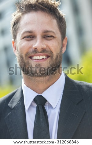 A young successful man, male executive businessman with beard smiling in front of a high rise office block in a modern city - stock photo