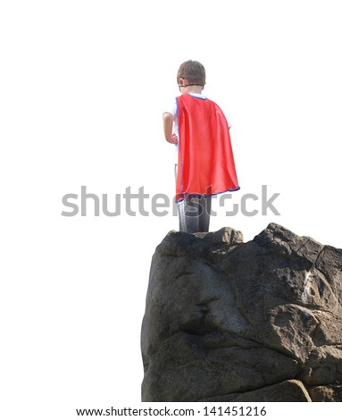 A young super hero boy is wearing a red cape and standing on a rocky cliff looking at a white isolated background for copyspace. - stock photo