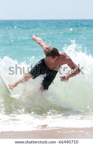 a young surfer riding the waves in the sea spray - stock photo