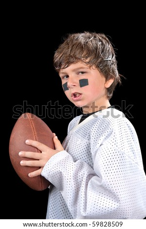 A young, sweaty quarterback football player holds his football and gives an attitude. - stock photo