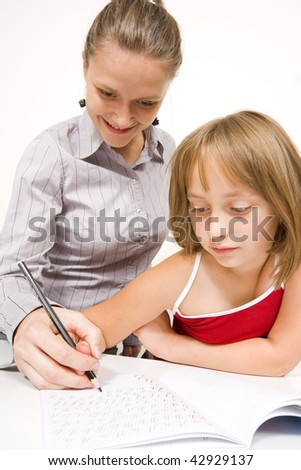 A young teacher and student learning to write together, the teacher helping her student - against white wall. - stock photo
