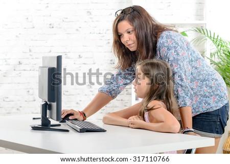 a young teacher helps a schoolgirl on a computer - stock photo