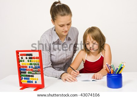 A young teacher or could be mother, helping a little girl to learn, both of them paying attention on the little student 's action against white wall. - stock photo