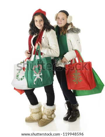 A young teen and her preteen friend dressed for winter and carrying filled Christmas shopping bags.  On a white background. - stock photo