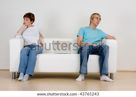 A young teen couple sitting on opposite ends of a sofa, not talking and ignoring each other.  Theme: non-communication.