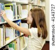 A young teen girl choosing a book from the school library shelves.  Shallow depth of field with focus on her face. - stock photo