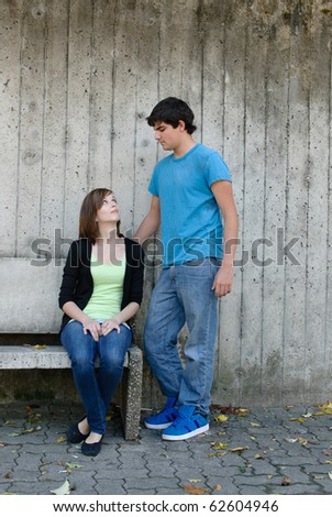 A young teen girl is sitting on a bench while staring up at her boyfriend - stock photo