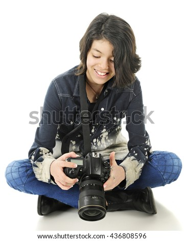 A  young teen photographer happy with the image she sees in the back of her pro camera.  On a white background. - stock photo