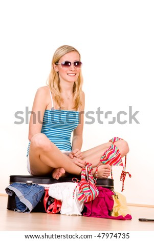 A young teenage girl sitting on a suitcase she is packing with bathing suits and summer clothing.  Possible themes:  spring break, vacation, summer travel - stock photo