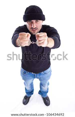 a young thief or burglar with handcuffs on - stock photo