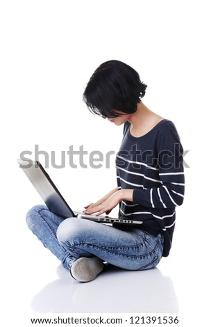A young thoughtful woman with a laptop sitting isolated on white background - stock photo