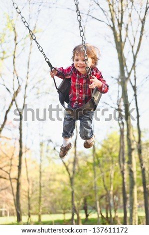 A young toddler boy swinging in the fall. - stock photo