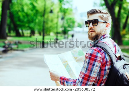 A young tourist with a beard holding a map and looking to the side in the alley in the park, rear view - stock photo