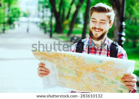 A young tourist with a beard laughing and looking at the map in the alley in the park - stock photo