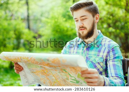 A young tourist with a beard smiling and sitting on a bench in the park, looking at the map, close-up - stock photo