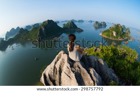 A young traveler girl sit on the top of mountain in Halong bay and enjoy the beauty of seascape. Young girl love wild life, travel, freedom. - stock photo