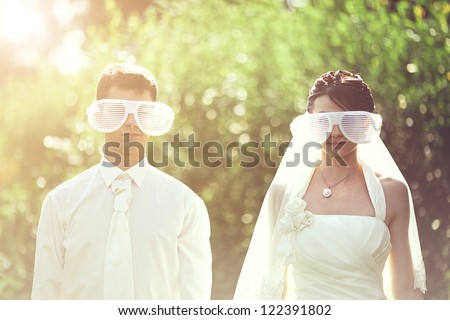 a young wedding couple couple in funny big glasses - stock photo
