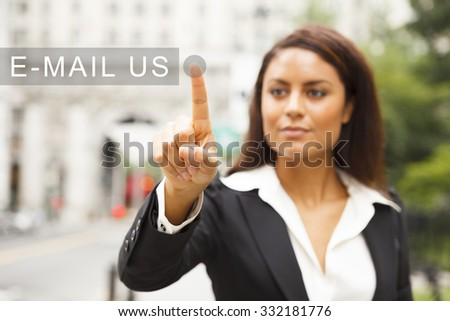 A young well dressed woman on a city street presses a virtual E-MAIL US button suspended in mid-air. - stock photo