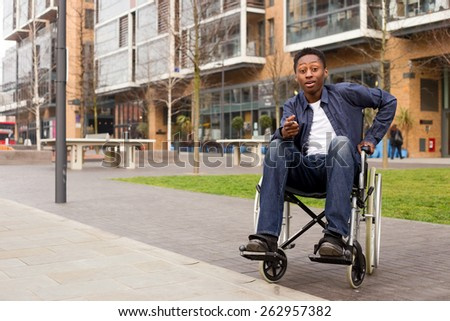 a young wheelchair user looking surprised.  - stock photo