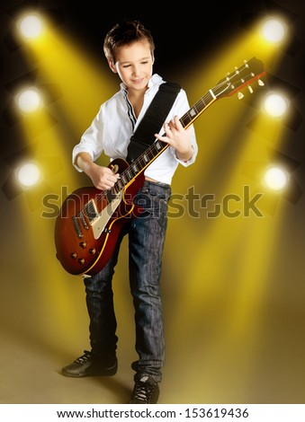 A young white boy playing on the electric guitar on the stage with bright yellow projector behind him - stock photo
