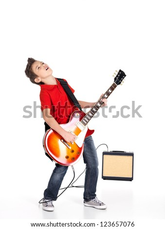 A young white boy sings and plays on the electric guitar with bright emotions, isolated on white background - stock photo