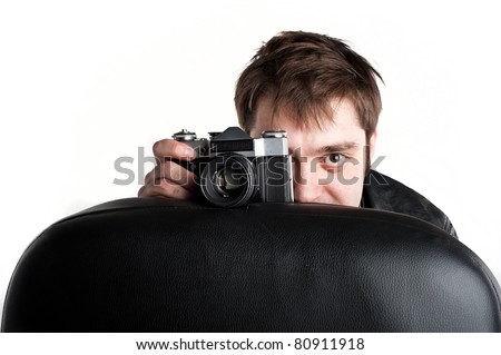 A young white Caucasian guy in a black leather jacket sitting on a chair and with a cheerful expression on his face holding a camera isolated over white - stock photo